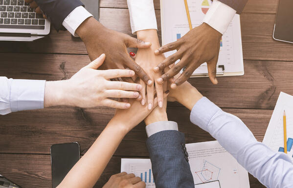 Diverse employees all places their hands on top of one another