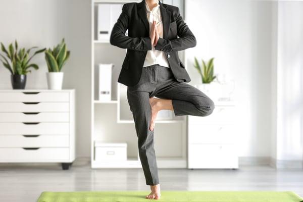 Employee doing yoga in their work attire